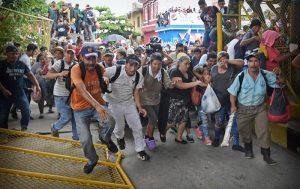 Migrantes rompen cerco y cruzan la frontera mexicana